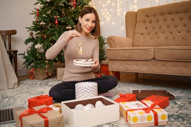 Femme emballage cadeau de noël assis sur la carpée dans le salon