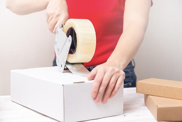 Femme, emballage, carton, boîtes, utilisation, ruban, dérouleur