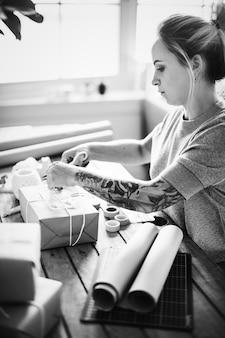 Femme emballant la boîte de colis par elle-même