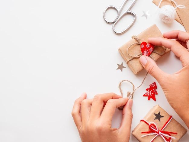 Femme emballant des cadeaux de noël et du nouvel an dans du papier kraft cadeaux attachés avec des fils blancs et rouges.