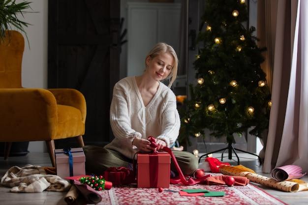 Femme emballant des cadeaux de noël à la maison sur un étage.