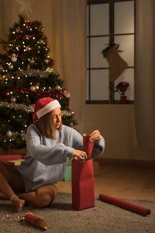 Femme emballant des cadeaux pour noël tout en portant un bonnet de noel