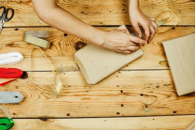 Une femme emballant des coffrets cadeaux de noël faits maison. faites des cadeaux de noël. cadeaux de noël à faire soi-même pour les amis et la famille