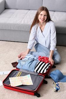 Femme emballant sa valise rouge dans le salon
