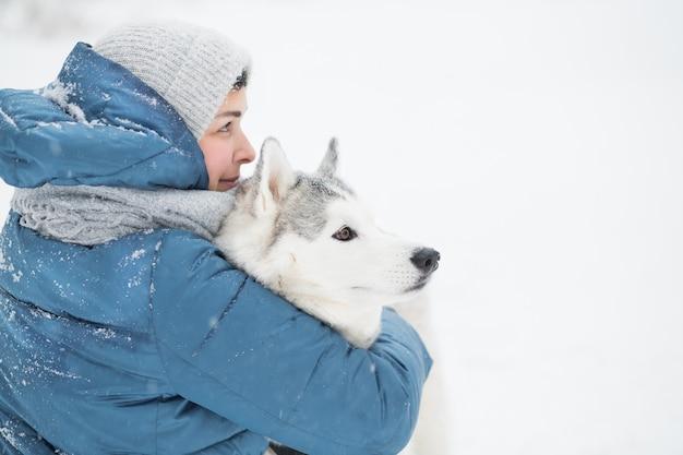 Femme embrassant un husky sibérien enneigé en hiver. gros plan portrait. chien. photo de haute qualité