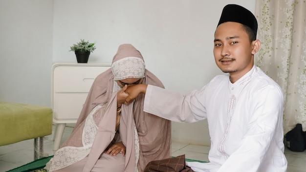Femme embrassant la main de son mari après le culte ensemble à la maison