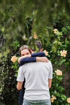Femme embrassant son copain debout contre la plante à fleurs