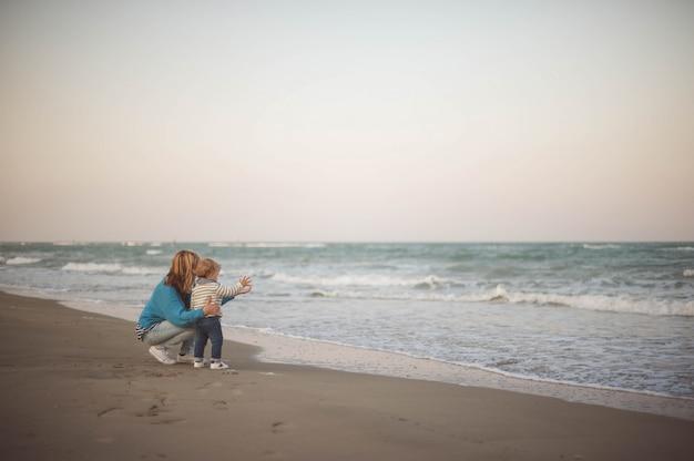 Femme embrassant son fils en regardant la mer