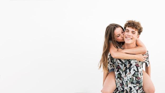 Femme embrassant son petit ami prenant le dos sur fond blanc
