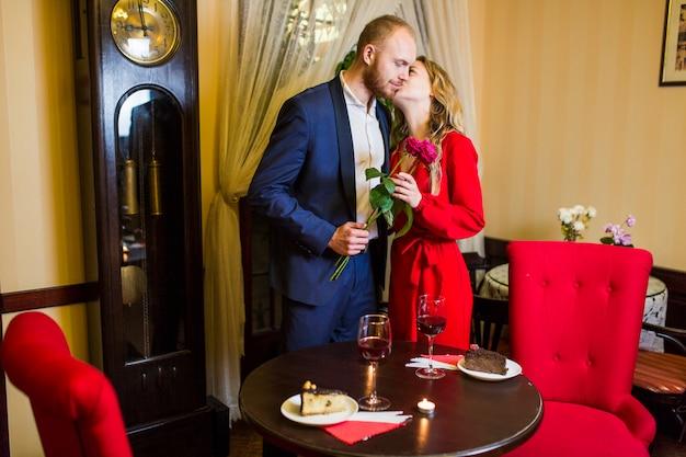 Femme embrasse un homme avec des fleurs sur la joue