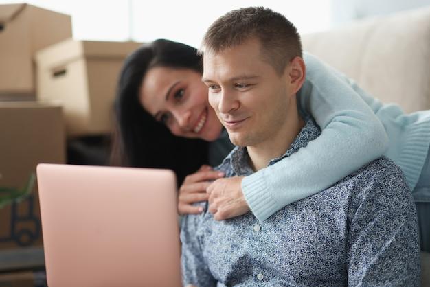 Femme embrasse l'homme sur fond de boîtes dans un appartement