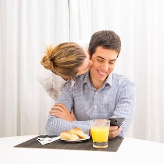 Femme embrasse son mari prenant son petit déjeuner à l'aide d'un téléphone portable