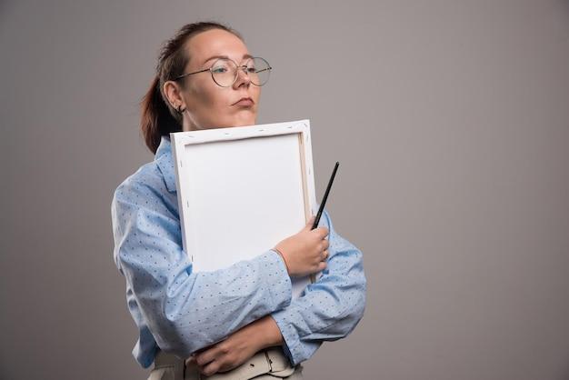 Une femme embrasse une toile vide avec un pinceau sur fond gris