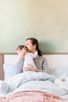 Femme, embrasser, bébé, bras, lit