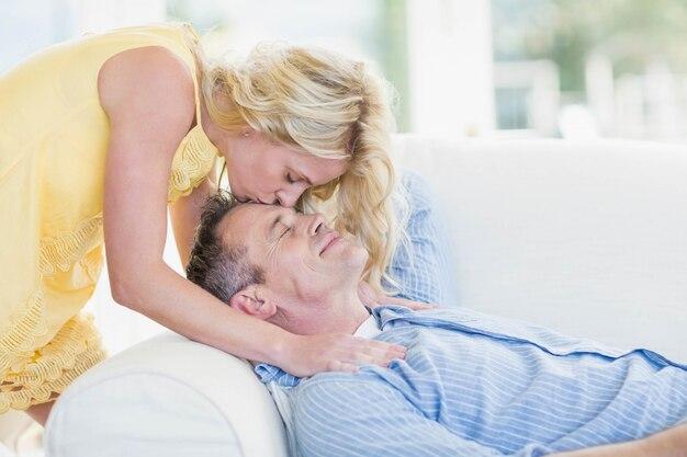 Femme embrasser mari sur le front dans le salon