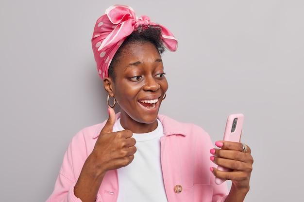 La femme a des émissions d'appel vidéo comme signe à la caméra garde le pouce vers le haut tient un smartphone moderne vêtu de vêtements élégants isolés sur gris