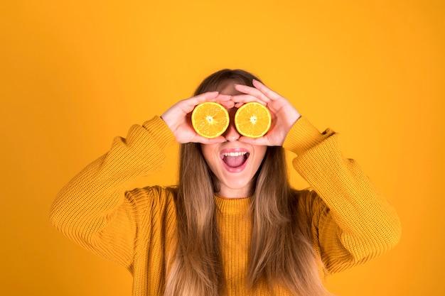 Une femme émotionnelle assez joyeuse avec un mur vibrant jaune isolé aux cheveux longs tient des morceaux d'orange dans ses mains. concept d'aliments sains. concept d'obsession des couleurs.