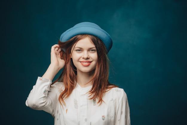 Femme émotionnelle au chapeau bleu gesticulant avec les mains chandail blond cheveux roux