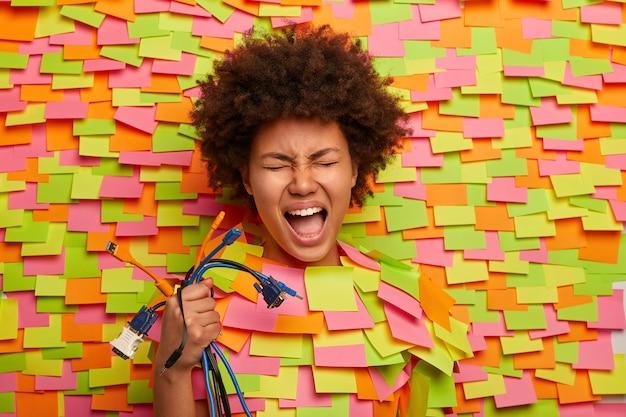Une femme émotionnelle a besoin de l'aide d'un technicien professionnel, détient de nombreux câbles colorés, ne sait pas comment connecter tous les cordons à l'ordinateur, sort la tête, entourée de nombreux autocollants, a la bouche ouverte