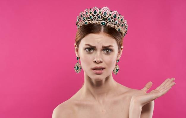Femme émotionnelle avec une couronne sur sa tête sur un modèle de princesse de fond rose. photo de haute qualité