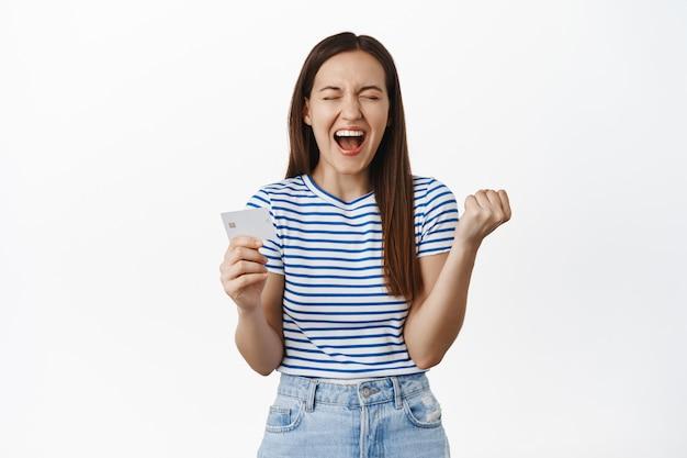 Une femme émotionnelle crie de bonheur et de satisfaction, montrant une carte de crédit, serrant le poing comme un champion, célébrant, debout sur un mur blanc