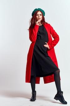 Femme émotionnelle dans un manteau rouge et avec un chapeau en pleine croissance sur un fond clair modèle de pose de bottes noires