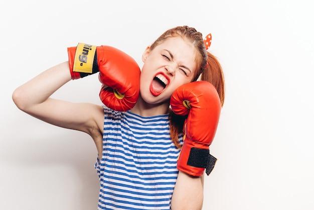 Femme émotionnelle dans un t-shirt rayé et des gants de boxe rit à la lumière.