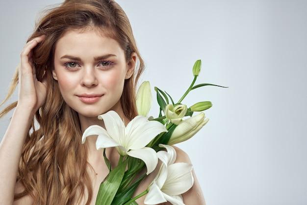 Femme émotionnelle avec des fleurs printemps modèle épaules nues peau claire.