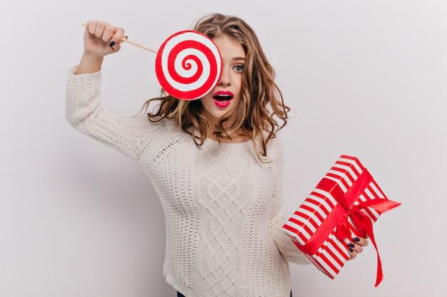 Femme émotionnelle avec joli maquillage et belle manucure, ferme un œil avec d'énormes bonbons au caramel