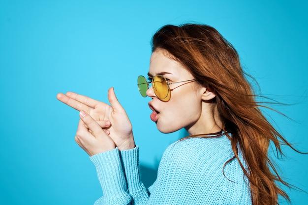 Femme émotionnelle avec des lunettes et un pull bleu lifestyle casual wear fond bleu.