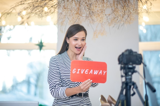 Femme émotionnelle positive montrant la surprise tout en ayant un cadeau sur son blog