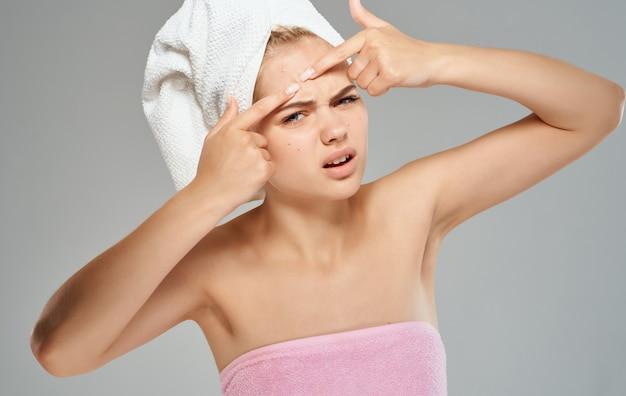 Femme émotionnelle serre les boutons sur son front et une serviette sur sa tête, épaules nues, vue recadrée.