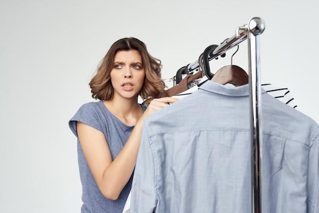 Femme émotionnelle shopaholic choisir des vêtements shopping en magasin fond isolé. photo de haute qualité