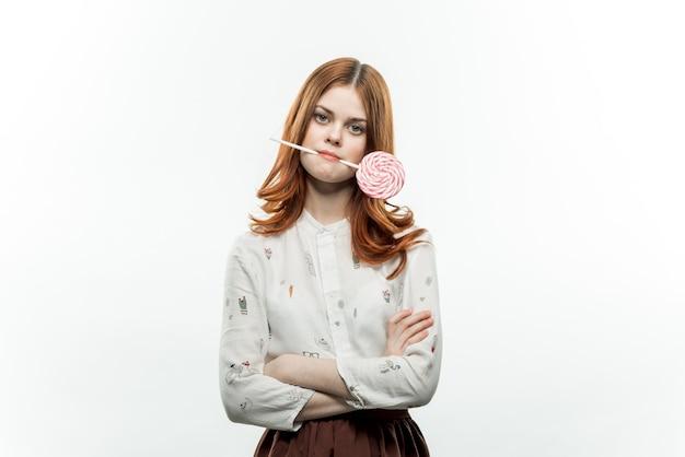 Femme émotionnelle tenant des bonbons sucette dans ses dents joie fond clair