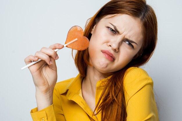 Femme émotionnelle tenant une chemise jaune sucette en forme de coeur isolé