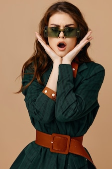 Femme émotionnelle tenant la main sur le visage lunettes de soleil costume mur isolé