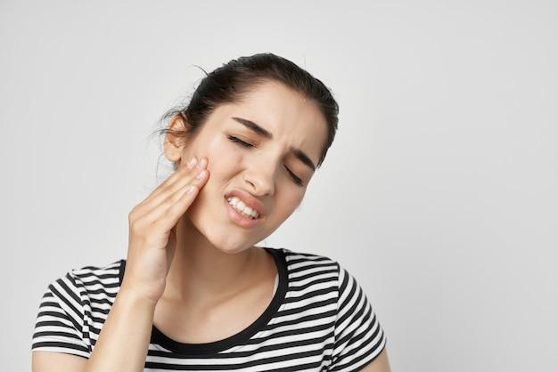 Femme émotionnelle tenant pour faire face à fond clair de soins de santé de maux de dents