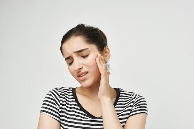 Femme émotionnelle tenant pour faire face à fond isolé de soins de santé de maux de dents