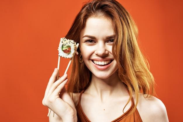 Femme émotive avec le casse-croûte de rouleaux de sushi de baguettes