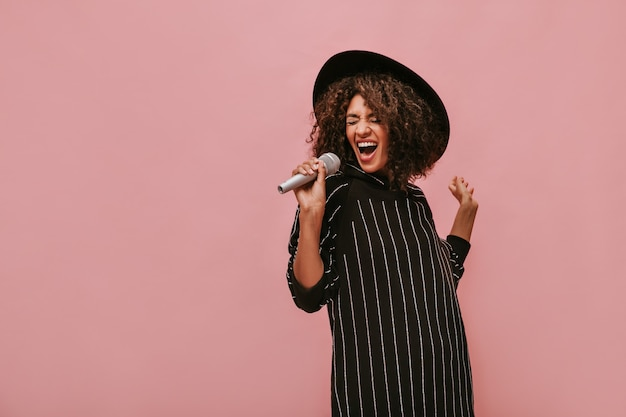 Femme émotive avec une coiffure brune frisée dans un chapeau élégant et une robe noire rayée tenant un microphone et chantant sur un mur rose.