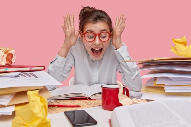 Femme émotive excitée lève les mains près du visage, garde la bouche largement ouverte, réagit aux informations étonnantes écrites dans le livre, porte des lunettes à jante rouge