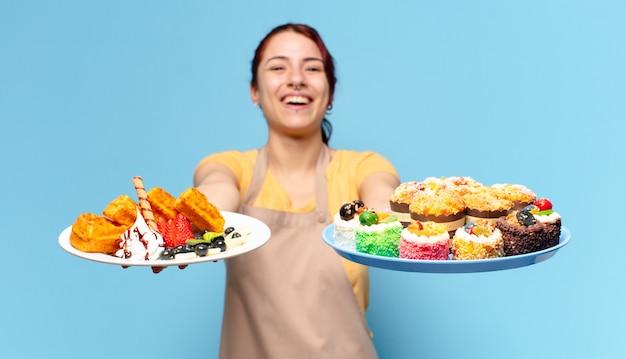 Femme employée de boulangerie tty avec des gaufres et des gâteaux