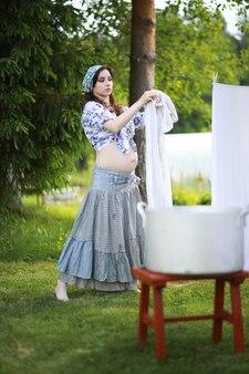 Femme enceinte accrochant des vêtements de lavage sur la corde pour le séchage