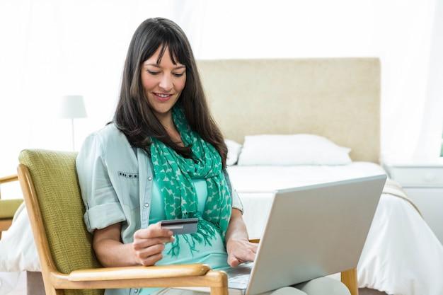 Femme enceinte, achats en ligne sur son ordinateur portable à la maison