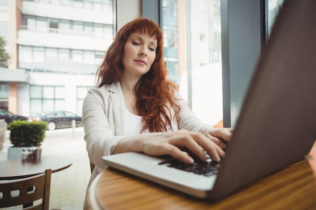 Femme enceinte à l'aide d'un ordinateur portable à la cafétéria