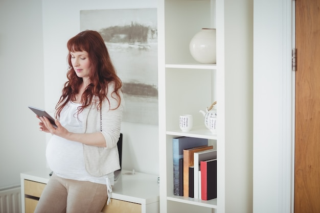 Femme enceinte à l'aide de tablette numérique dans la salle d'étude