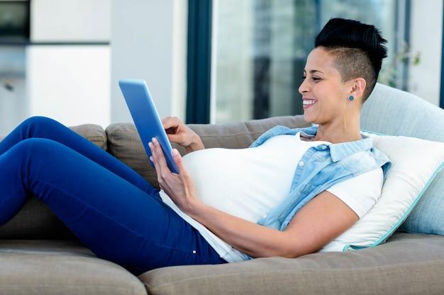 Femme enceinte à l'aide d'une tablette numérique tout en vous relaxant sur le canapé du salon