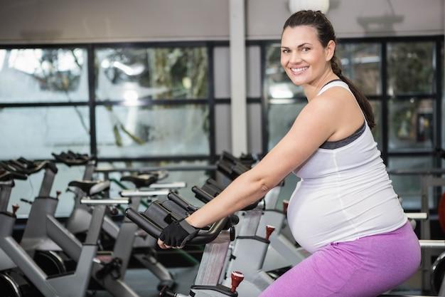 Femme enceinte à l'aide d'un vélo d'exercice au gymnase