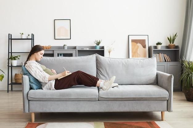 Femme enceinte allongée sur le canapé et prenant des notes dans son journal, elle se repose à la maison