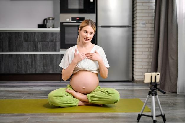 Une femme enceinte amicale s'assoit sur un tapis de fitness pour enregistrer une vidéo sur un smartphone